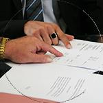 Foto de manos señalando un documento