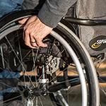 mano sobre rueda en silla de ruedas